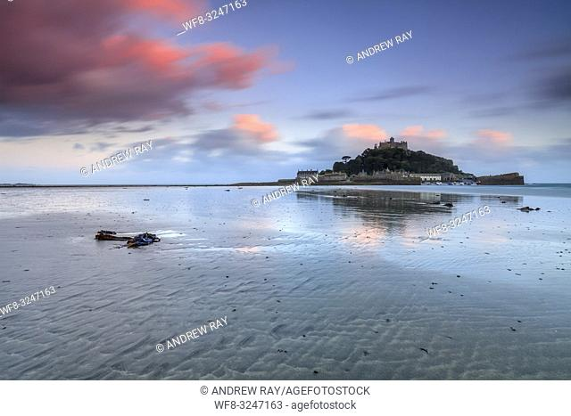 St Michael's Mount captured at sunset from Marazion Beach in Cornwall. A long shutter speed was utilized to blur the movement in the clouds