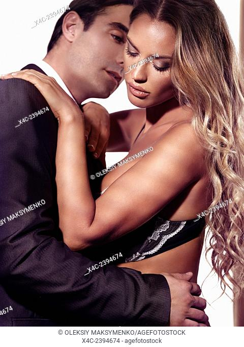 Young blond woman in lingerie and a man in suit about to kiss. Sexy couple portrait