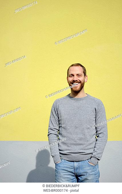 Portrait of laughing young man in front of yellow background