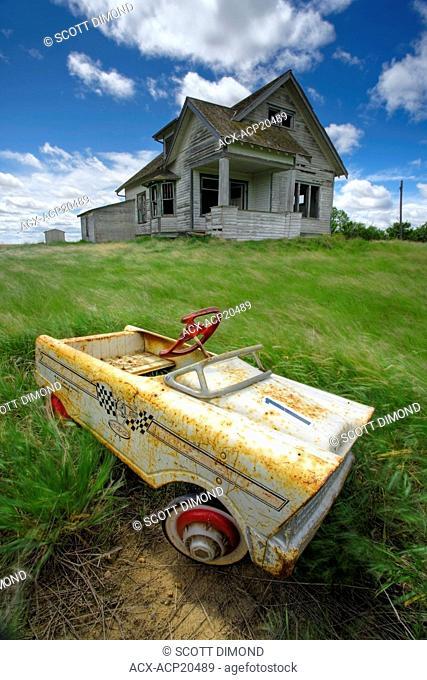 Abandoned farmhouse with child's pedal car, Saskatchewan, Canada