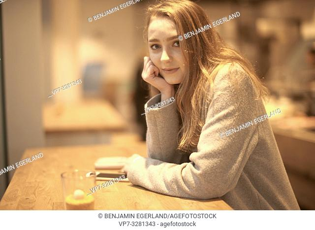 young woman sitting indoors in café, in Cottbus, Brandenburg, Germany