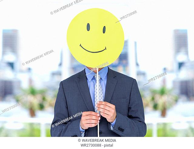 Businessman holding happy smiley face in front of her face against office in background