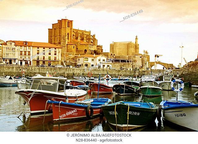 Fishing boats at port and Santa Maria de la Asuncion and castle in background, Castro Urdiales, Cantabria, Spain