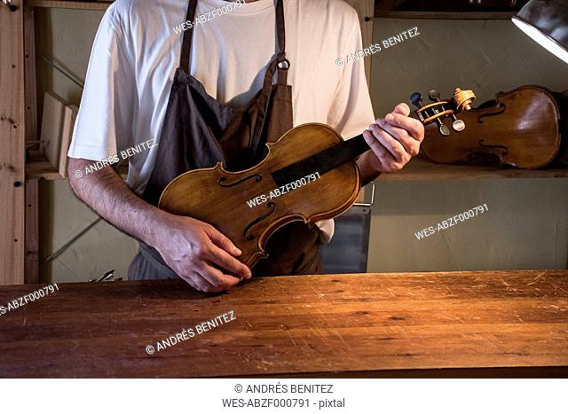 Luthier holding a violin in his workshop