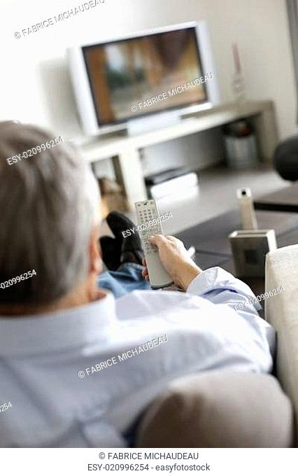 Back view of senior man in couch watching tv