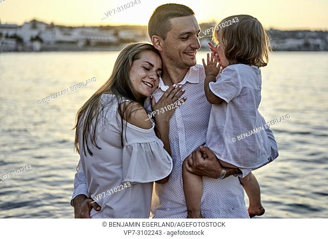 candid family, unposed, real people, sunset, love, bonding, at beach, seaside. In Chersonissos, Crete, Greece