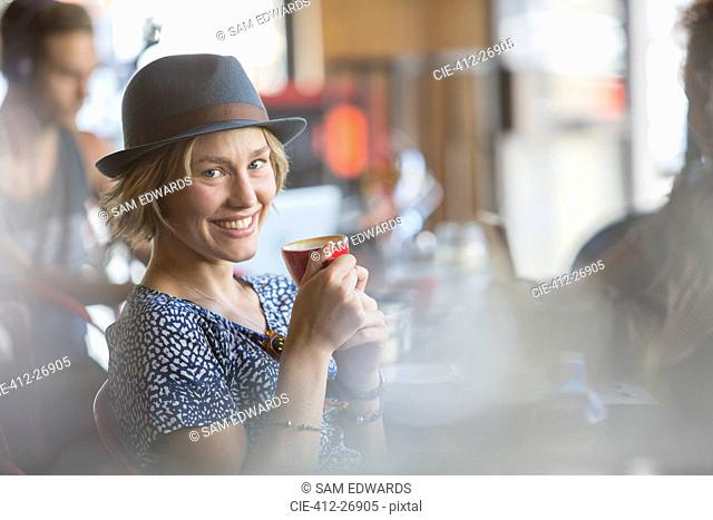 Portrait smiling woman in hat drinking espresso in cafe