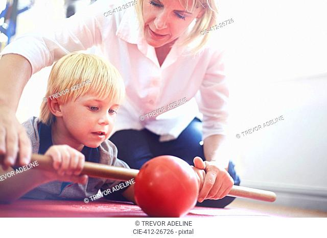 Physical therapist guiding boy rolling ball with stick