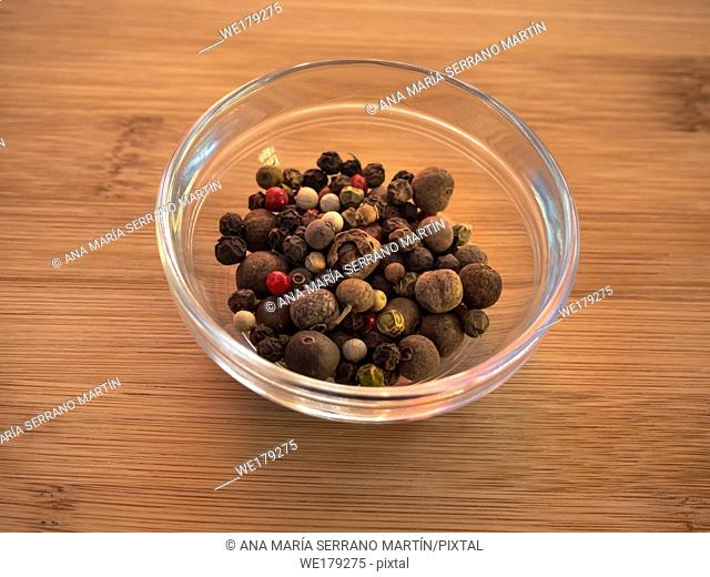 Crystal bowl with white peppercorns with five peppers mix on a wooden table