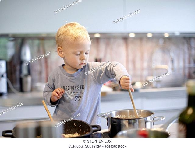 Toddler boy cooking in kitchen