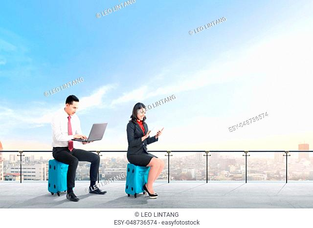 Young two asian business people sitting on blue suitcase hold the laptop and tablet working on modern terrace with city view and blue sky background