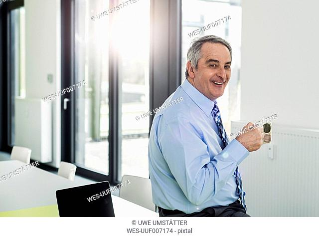 Senior manager with coffee cup in office