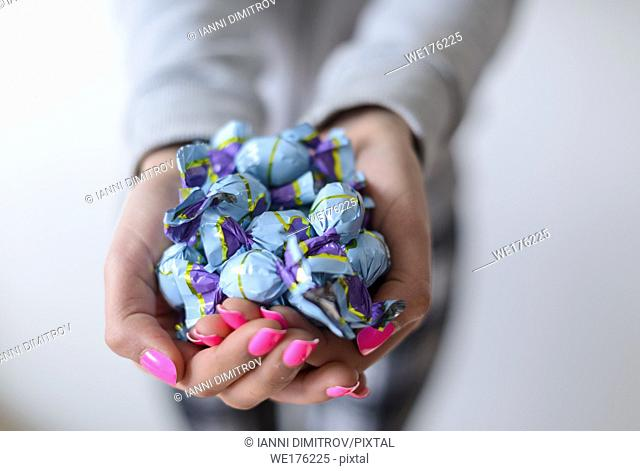 Selective focus-Girl with pink nail varnish hold wrapped chocholate sweets