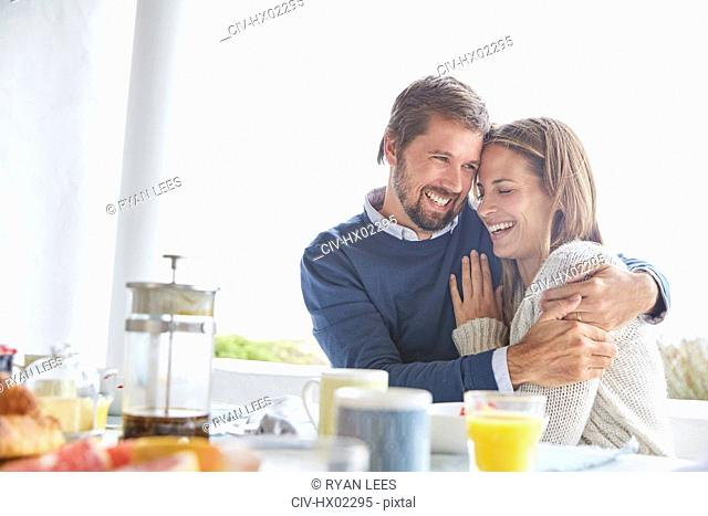 Smiling affectionate couple hugging at patio breakfast table