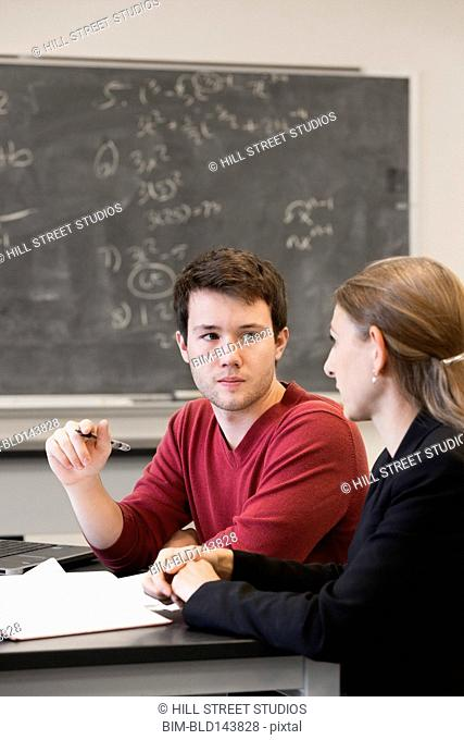 Caucasian student and teacher talking in classroom