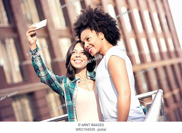 Two women posing and taking a selfie by a large building in the city