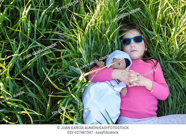 Little girl and her doll lying on green cereal field at sunset, Spain