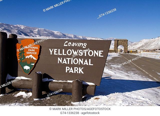 Entrance/exit sign at North Entrance of Yellowstone National Park, Roosevelt Arch visible in background, Montana, USA