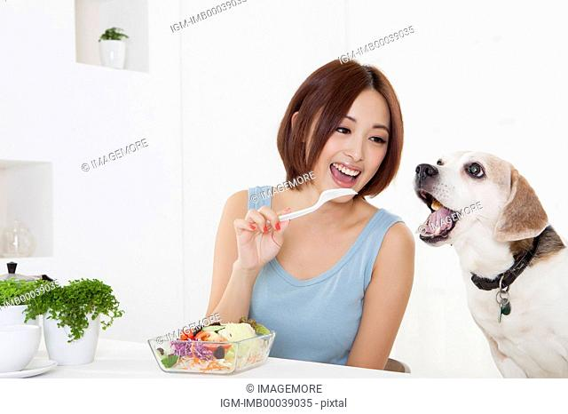 Young woman looking at dog with smile