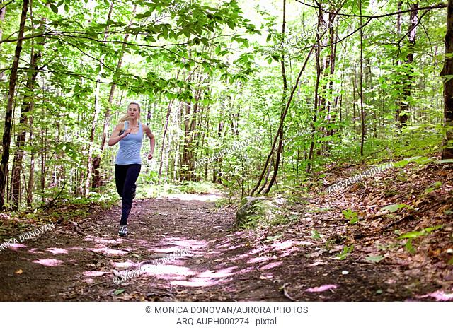 Fit young woman trail running on trails through woods at mount sabattus