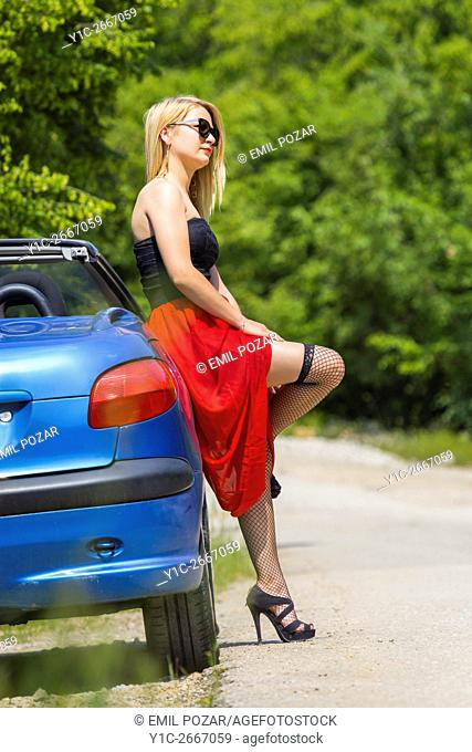 Young blond woman and Blue car