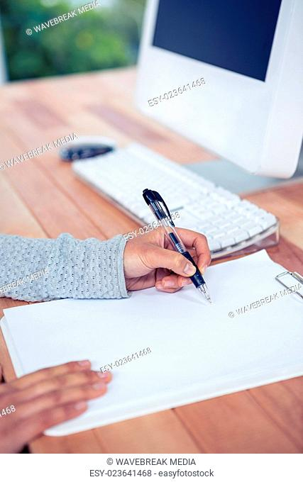 Womans hand writing with pen on white sheet