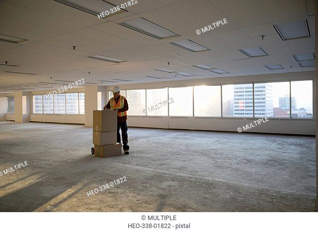 Construction worker with cardboard boxes in sunny empty, unfinished highrise office
