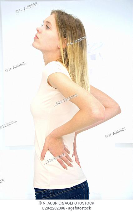 Young beautiful blond girl with both hands on her painful back
