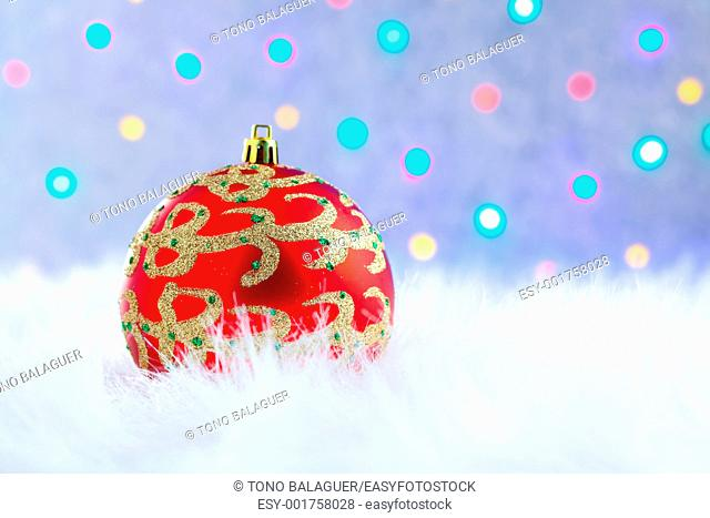 christmas bauble on white fur and colorful lights