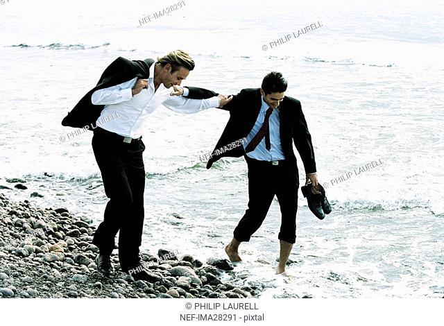 Two men wearing suits walking on beach