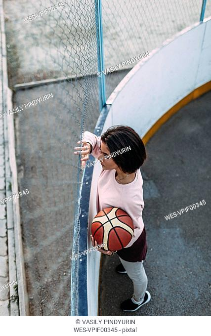 Young woman standing with basketball at fence