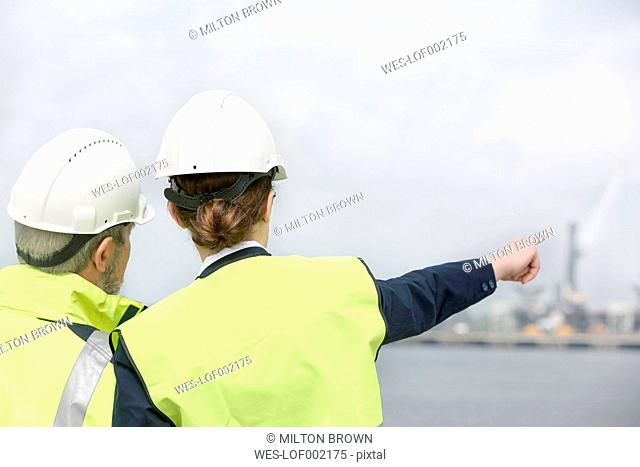 Man and woman talking at container port