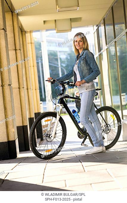Young woman holding a bicycle