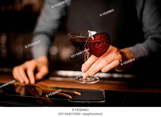 Bartender holding a glass of red alcoholic drink, decorating with a thin slice of beet