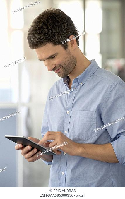 Man lost in thought using digital tablet