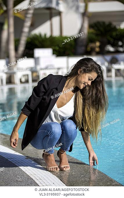 Elegant executive girl in jacket relaxing on hotel territory and touching water in refreshing pool and smiling