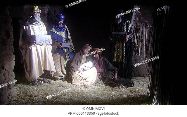 Virgin Mary sitting on straw floor holding baby Jesus with Joseph and three wise men standing holding gifts