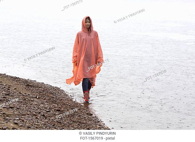 Woman wearing raincoat walking at lakeshore during rainy season