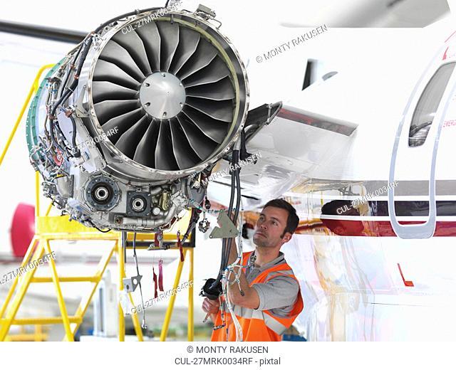 Engineer inspects jet engine