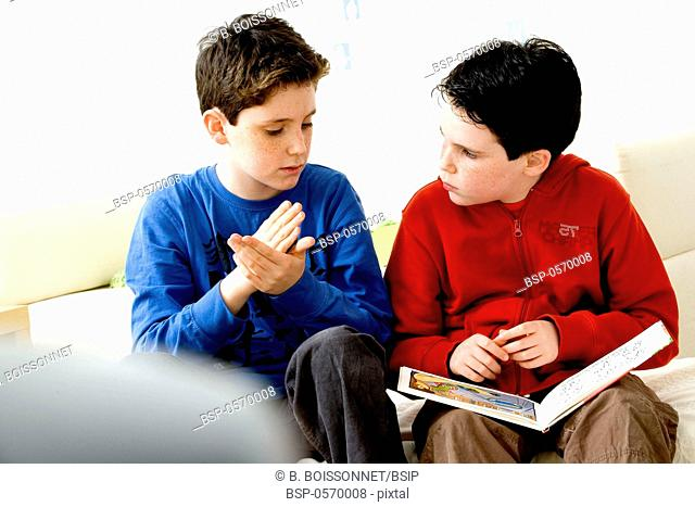 SIGN LANGUAGE Models. Do not use for HIV. A young hearing-impaired boy and his brother using the French sign language with the aid of a book