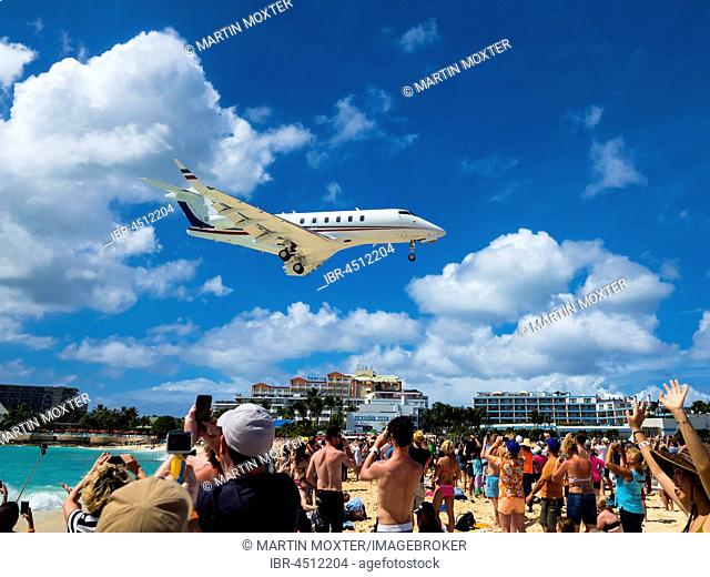 Tourists watching and photographing an airplane landing over Maho Beach, at Princess Juliana International Airport, Simson Bay Village, Philippsburg, Caribbean
