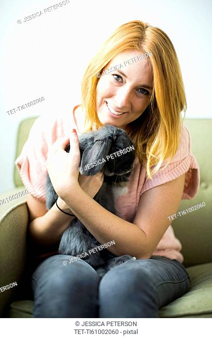 Woman sitting on sofa embracing rabbit