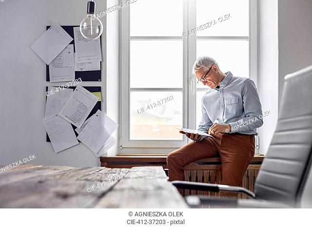 Businessman using digital tablet in office window