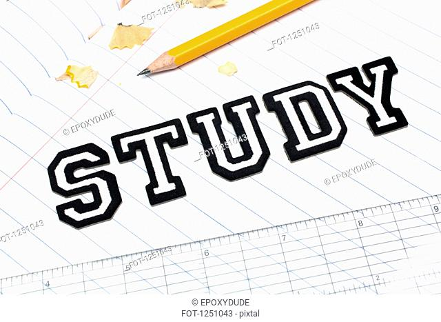 Varsity font stickers spelling out Study atop a lined paper notebook with ruler and pencil