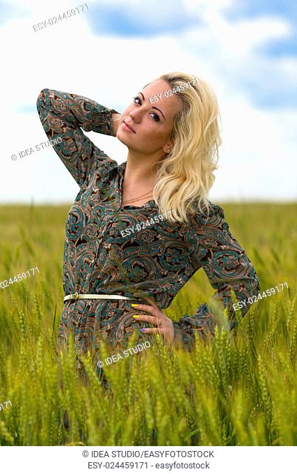 Attractive young blonde woman in rye field