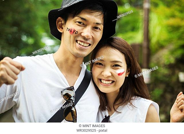 Portrait of man wearing hat and young woman with brown hair, Japanese flag painted on her cheek, smiling at camera