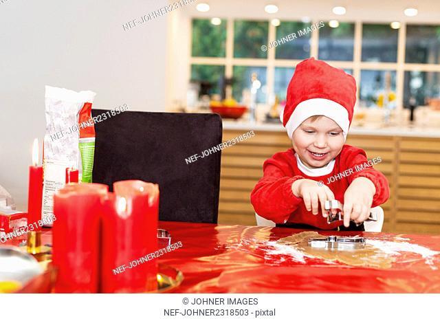 Boy baking gingerbread cookies