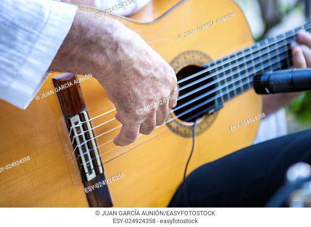 Spanish flamenco guitarist playing. Selective focus on hand