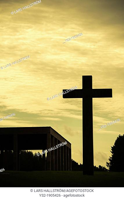 Night sky and silhouette of big christian cross and Chapel of the holy cross at skogskyrkogarden cemetery in Stockholm, Sweden