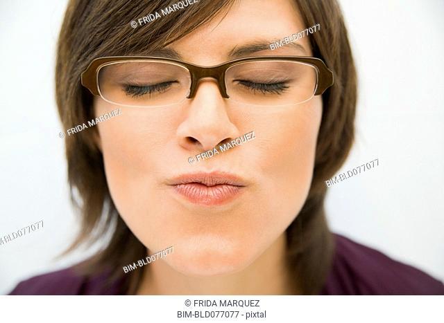 Hispanic woman in eyeglasses puckering for kiss